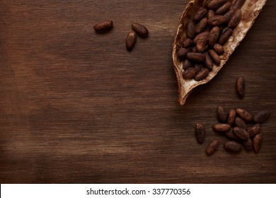 Roasted cocoa beans in the dry cocoa pod fruit on a dark wooden table
