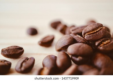 roasted coffee bean on light brown wooden texture with copy space, selective focus