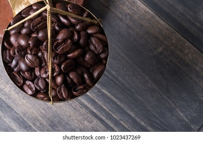 Roasted coffee bean on weight scale on wooden table top.