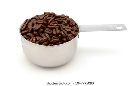Roasted coffee beans in an American cup measure, on a white background