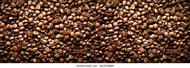 Roasted coffee beans background. Cappuccino, aroma black caffeine drink ingredient for coffee beverage