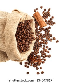 Roasted coffee beans in bag with anise star and cinnamon sticks. Isolated on white