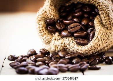Roasted coffee beans in bag on wooden background in vintage color style