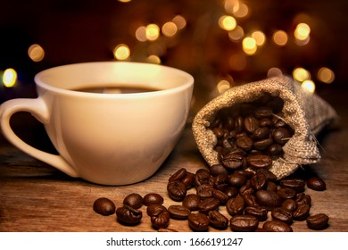 Roasted coffee beans and bags placed on a wooden table, white coffee mugs. The background is a yellow light bokeh that gives a warm feeling.