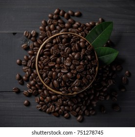 The roasted coffee beans in the bowl on the wooden table.