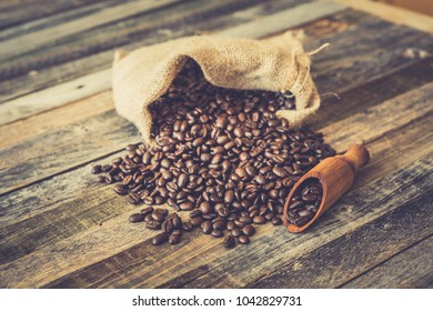 Roasted coffee beans in a burlap bag on wooden table background