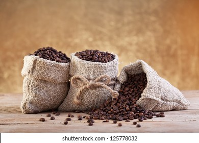 Roasted coffee beans in burlap bags on old table