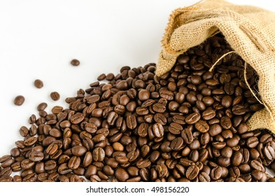 Roasted coffee beans in burlap sack bag over white background