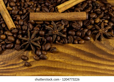 Roasted coffee beans, cinnamon sticks and star anise on rustic wooden background