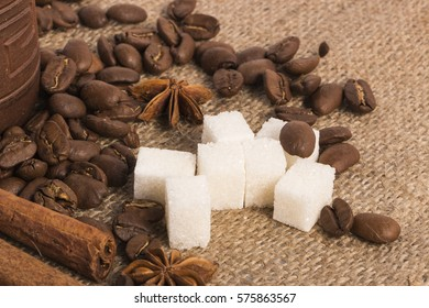 roasted coffee beans, cinnamon and sugar on a background of burlap