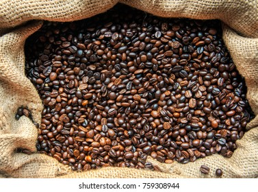 Roasted coffee beans. Coffee beans close-up, background. A warehouse of bags full of delicious, delicious coffee