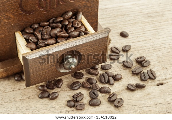 roasted coffee beans in drawer of coffee grinder