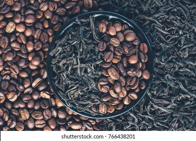 roasted coffee beans and dry leaves of black tea, top view closeup