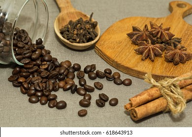 Roasted coffee beans in glass jar and some spices - cinnamon, clove and anise prepared for cooking
