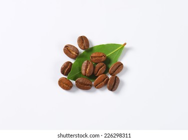 roasted coffee beans with green leaves