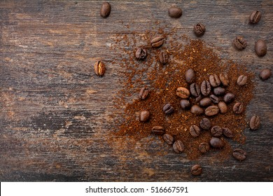 Roasted coffee beans and ground coffee on old wood table top view for text,copy space and background.