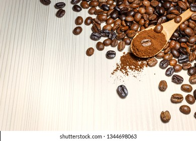 Roasted coffee beans and ground coffee in wooden spoon on light table. Close-up view with space for text.