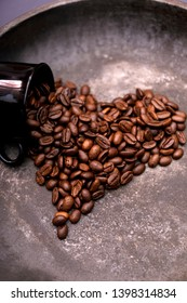 Roasted coffee beans in hearth shape. Hearth made of coffee beans, love coffee concept. Vintage photo with old rusty frying pan.