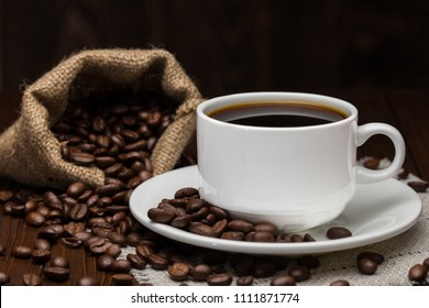Roasted coffee beans in little bag and cup of coffee with drink on dark wooden surface.