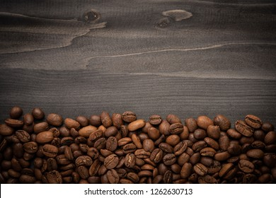 Roasted coffee beans on dark wood  background