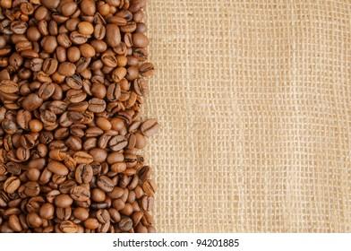 Roasted coffee beans on jute hessian background