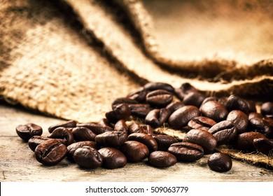 Roasted coffee beans on old wood background. Macro shot
