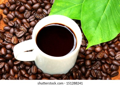 Roasted coffee beans on wood and black coffee.