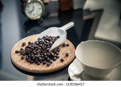roasted coffee beans on wooden background and coffee cup on table