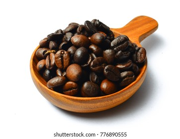 Roasted coffee beans on wooden scoop isolated on white background.