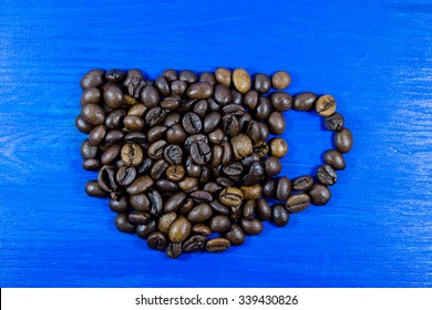 Roasted coffee beans placed in the shape of a cup on blue wooden background