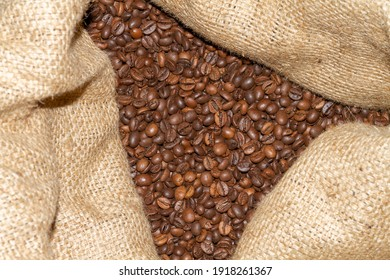 Roasted coffee beans of the Robusta variety inside the cloth bag.
