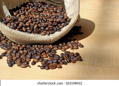 roasted coffee beans in sack bag on wooden table