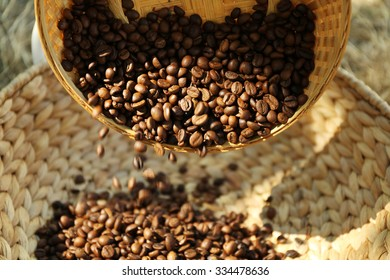 Roasted coffee beans scatter from wattled basket into the other one