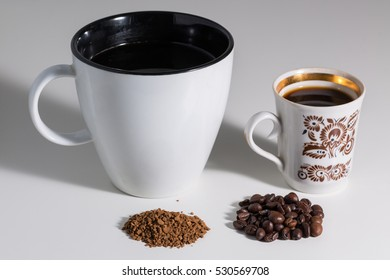 Roasted coffee beans in a small Cup and ground coffee in a large mug