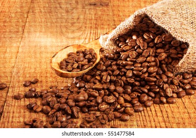 Roasted coffee beans in small sack and cup of coffee over on wooden table.