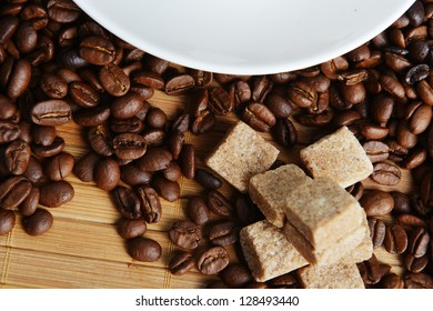 Roasted coffee beans and sugar on wooden background