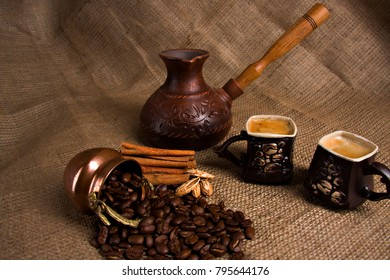 Roasted coffee beans with two cups of coffee and spices on the bag.