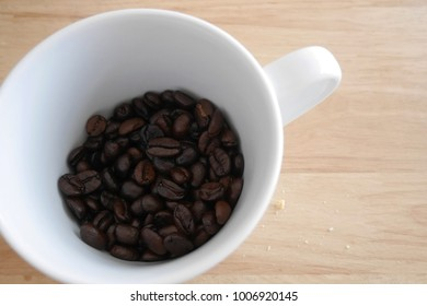 Roasted coffee beans with white cup on wooden