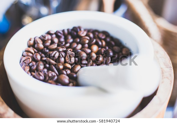 Roasted coffee beans in a white cup.