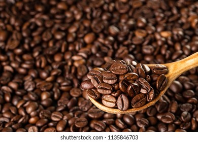 Roasted coffee beans in a wooden spoon. Food ingredients,  space for text