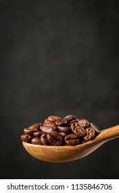 Roasted coffee beans in a wooden spoon on gray background.  Food ingredients,  space for text
