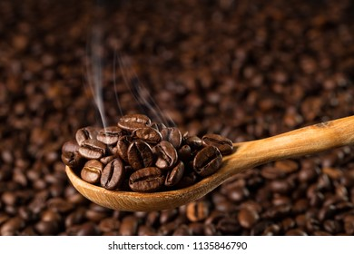 Roasted coffee beans in a wooden spoon in the smoke. Food ingredients,  with copyspace for your text. Selective focus
