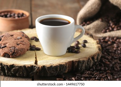 Roasted coffee grains and a cup of coffee and cookies on a brown wooden background. Robusta, Arabica.