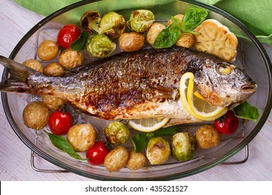 Roasted dorado fish with brussels sprouts, tomatoes, garlic, young potato and greens. View from above, top studio shot