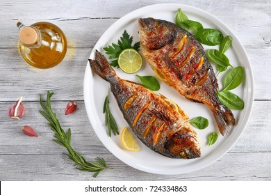 roasted dorado or sea bream fish with lemon and orange slices, spices, fresh parsley and spinach on white platter on old wooden table with ingredients on background, horizontal view from above