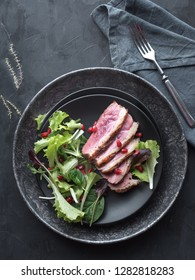 Roasted duck breast with green salad and pomegranate on black plate. Overhead view.