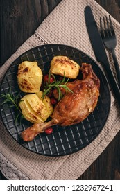 Roasted duck legs with apples and cranberries.