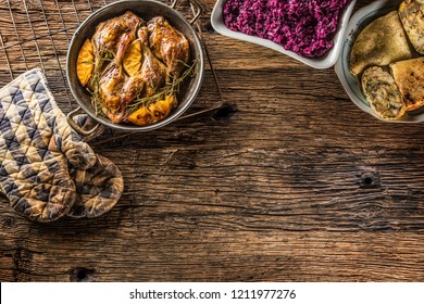 Roasted duck legs in pan with oranges herbs red cabbage and potato pankaces.