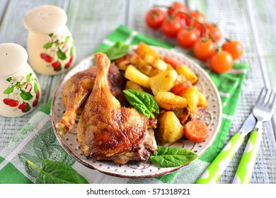 Roasted duck legs with potatoes and carrots on a plate with a hearty dinner on a bright green table