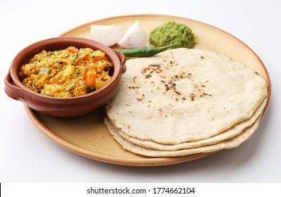 roasted egg plant and bhakri or Indian flat bread served with green chilli chutney traditionally called as Theccha in Marathi and spring onion beside the plate. A  Maharashtrian food